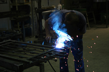 Welder in a workshop making a fence