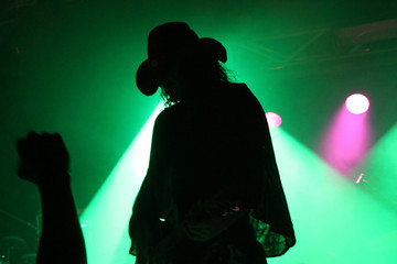 Silhouette of a guitarist on stage with a cowboy hat