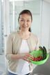 野菜を持ってキッチンに立つシニア女性
