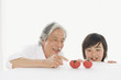 トマトを眺める祖父と孫