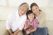 孫とソファに座る祖父母