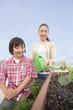 ベランダの植物に水をやる祖母と孫
