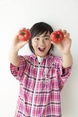 トマトを両手に持つ男の子