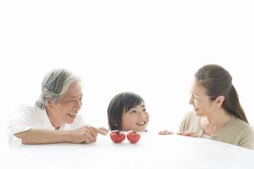 トマトを前に座る祖父母と孫