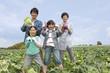 野菜を持って畑に立つ親子4人