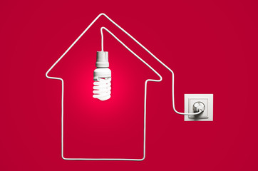 Glowing lightbulb in a house on a red background