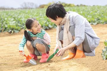 スコップで畑の土をいじる母と娘