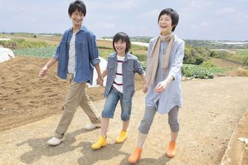 畑の中の道を歩く親子3人