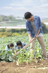 畑を耕す父と子供2人