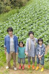畑の前に立つ親子4人