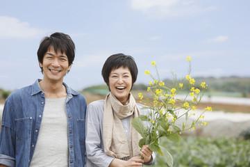 畑の前で菜の花を持って立つ男女