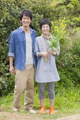 菜の花を持って立つ男女