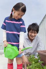 ベランダで植物に水を遣る父と子
