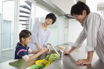 野菜を洗う親子3人