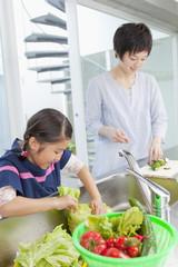 野菜を洗う母と娘