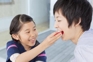 母にトマトを食べさせる娘