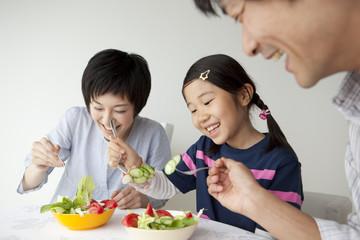 野菜を食べる親子3人