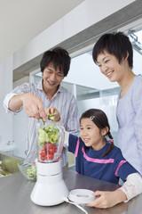 野菜ジュースを作る親子3人