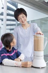 野菜ジュースを作る母と娘