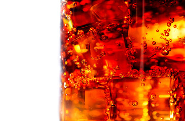 Cola with ice and bubbles in glass closeup