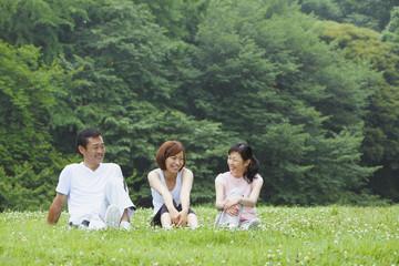 公園で座る中年男女と若い女性