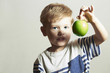 Child holds the apple.Little Boy with green apple.food.Fruits