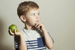 Child with apple.Little Boy.Health food.Fruits.Enjoy Meal
