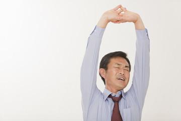 伸びをする中年男性