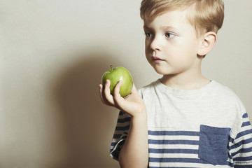 Child holds the apple.Little Boy.Health food.Fruits.Enjoy Meal