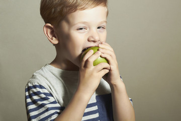 Child eating apple.Little Boy.Health food. Fruits. Enjoy Meal