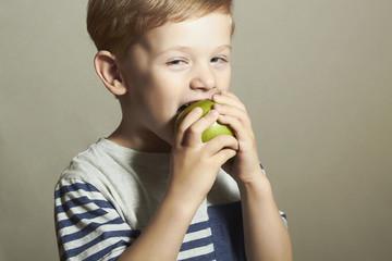 Child eating apple.Little Boy.Health food. Fruits. Enjoy Meal
