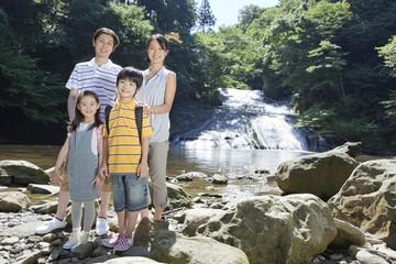 渓流に立つ家族4人
