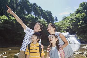 渓流で上を見上げる家族4人