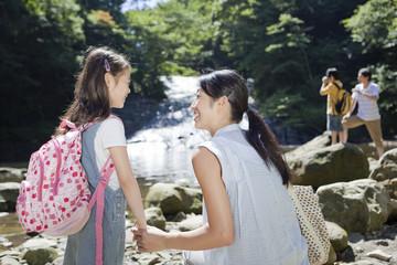 渓流で娘の手を握る母親