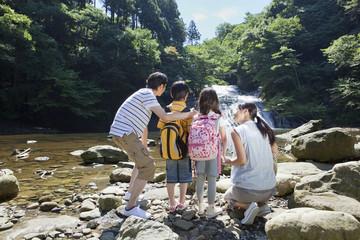 渓流に立つ家族4人の後姿