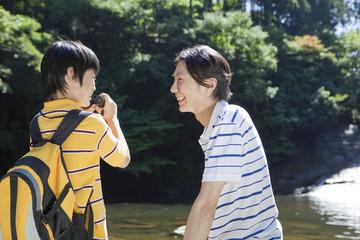 渓流で向かい合う父親と息子