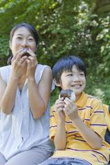 屋外でおにぎりを食べる母親と息子