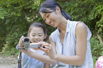 屋外でビデオカメラを見る母親と娘
