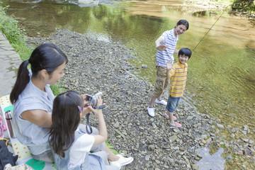 川辺で記念撮影をする家族4人
