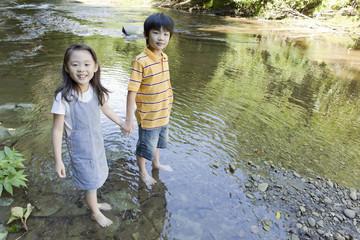 渓流で水遊びをする男の子と女の子