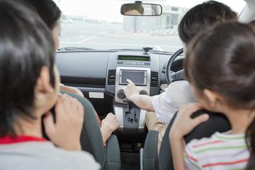 車の中でカーナビを見る家族4人