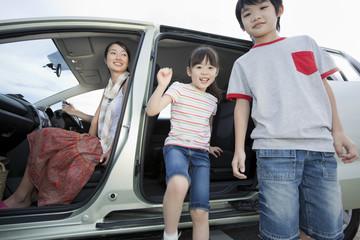 車から降りる子供2人と母親