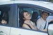 運転席で肩を揉む女性と家族