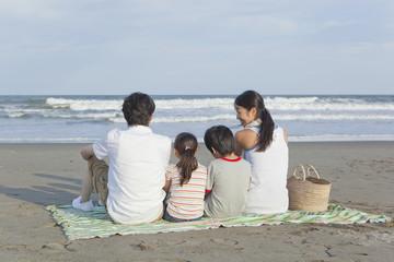 砂浜に座る家族4人の後姿