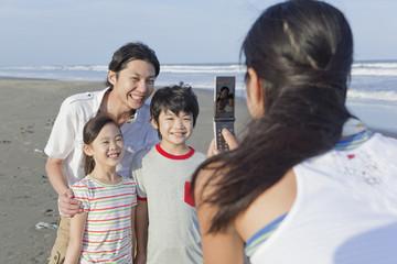 海岸で写真撮影をする家族4人