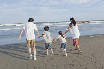 砂浜を手を繋いで走る家族4人の後姿