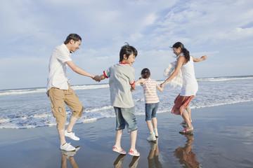 波打ち際で遊ぶ家族4人