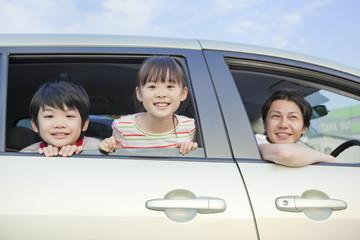 車の窓から顔を出す父親と子供2人