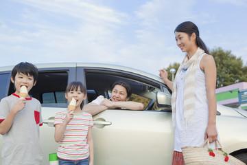 ソフトクリームを食べる子供2人と両親