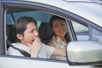 車の運転中にあくびをする男性